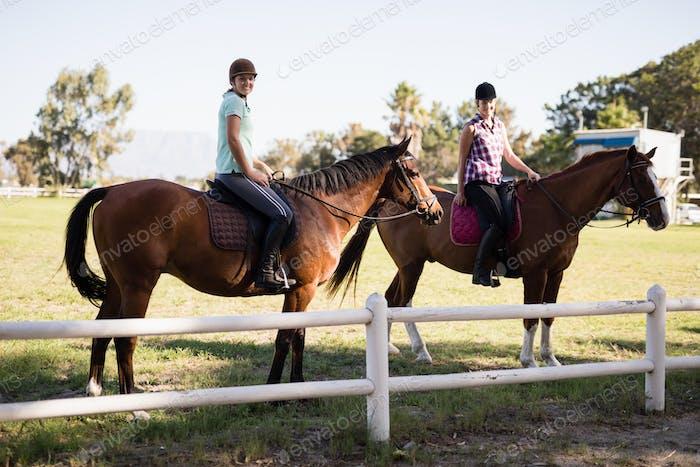 Portrait of female friends horseback riding