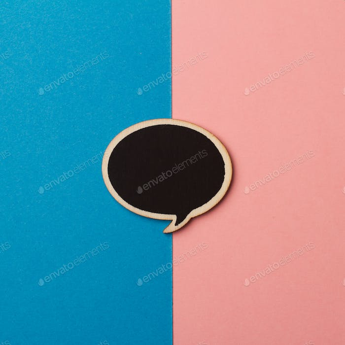 Round empty chalkboard wooden speech bubble on pink and blue