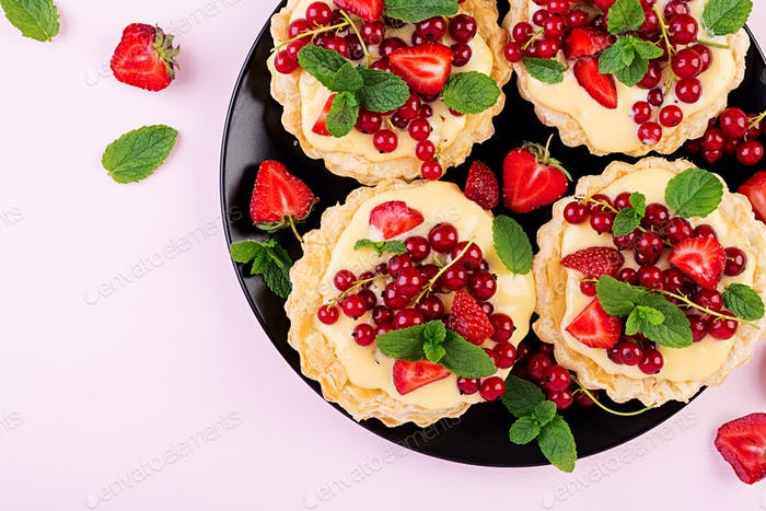 Tarts with strawberries, currant and whipped cream decorated with mint leaves. Top view