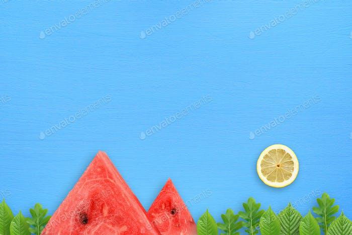 Conceptual Horizontal de verano con sandía, limón y hojas verdes sobre mesa azul
