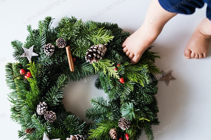 Feet of a baby stepping on christmas wreath on a white background.