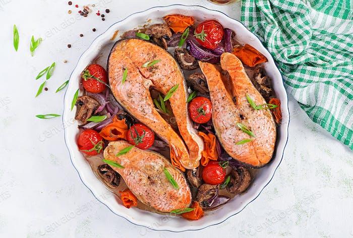 Gebackenes Lachsfischsteak mit Tomaten, Pilzen und roten Zwiebeln.