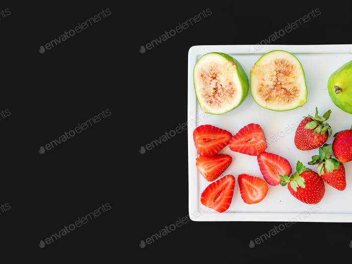 Fresh green figs and strawberries on a white ceramic board on bl