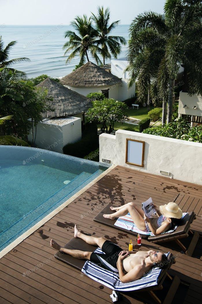 Couple sunbathing by the pool