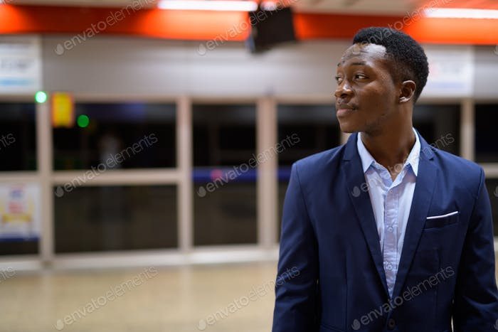 Profile view of young African businessman waiting in the subway train station