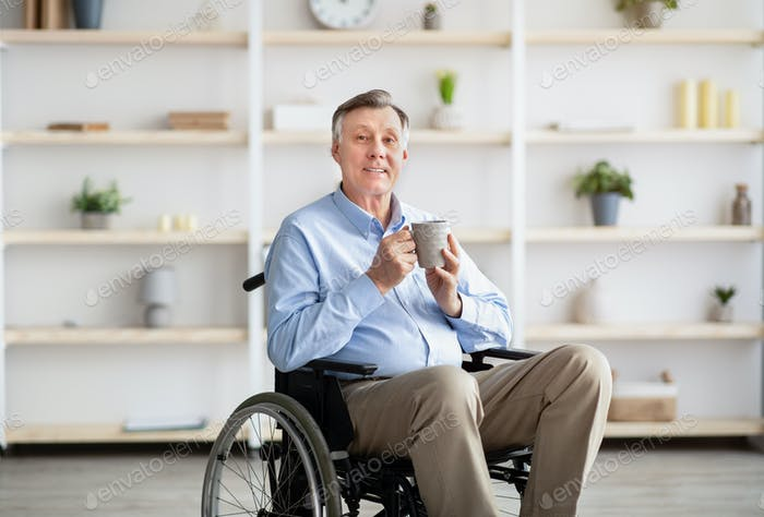Positive senior impaired man in wheelchair drinking coffee or tea at home
