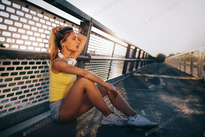 Portrait of fit cheerful blonde woman resting after a run in a city