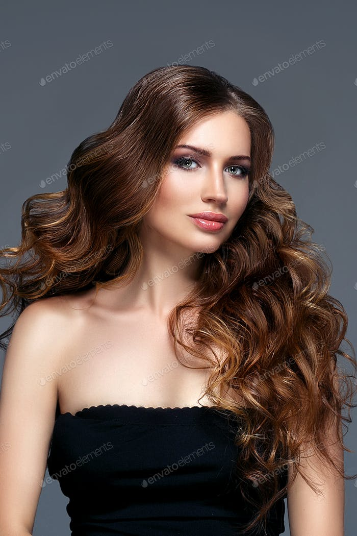 Beautiful woman with curly hairstyle portrait gray background. Female young beauty model girl face