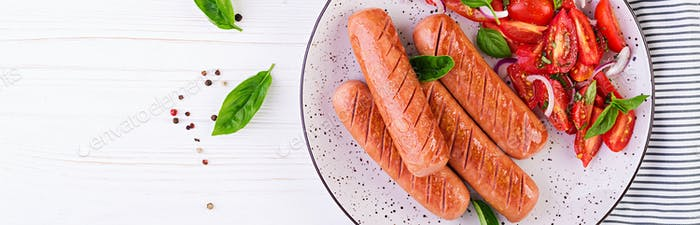 Grilled sausage with tomatoes, basil salad and red onions. BBQ m