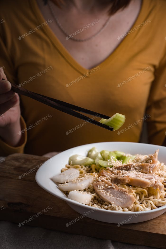 Woman eating celery sticks and ramen noodles