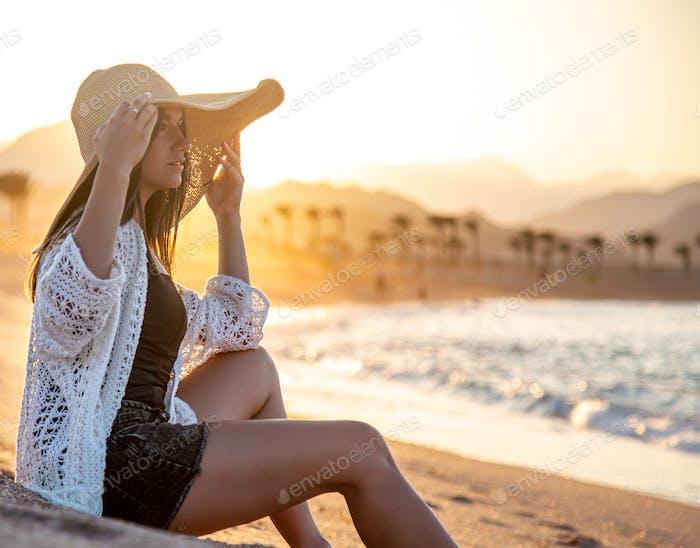 Hermoso modelo boho en un sombrero posa en la playa en el sol