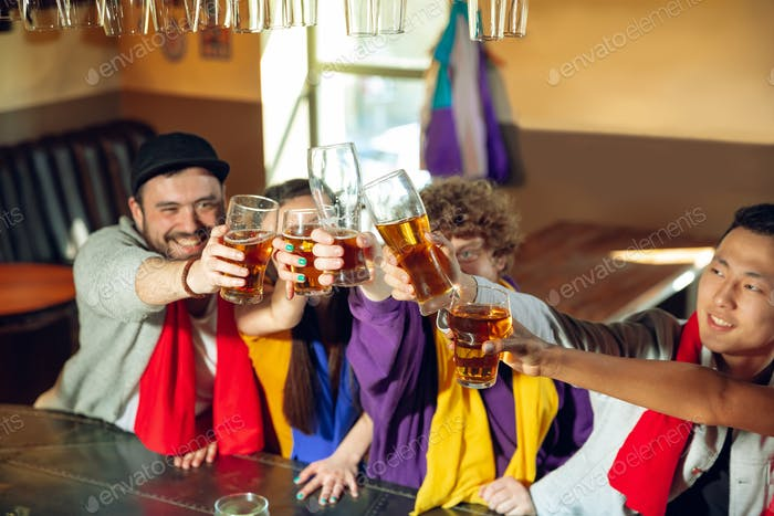 Sport fans cheering at bar, pub and drinking beer while championship, competition is going