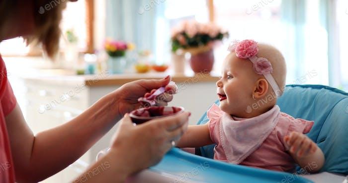 Pleasant young woman feeding a cute baby