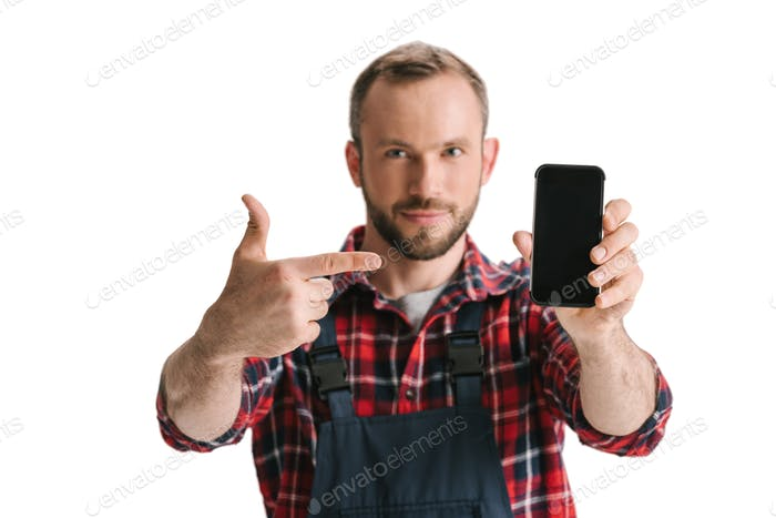 handsome man in overall pointing at blank smartphone isolated on white