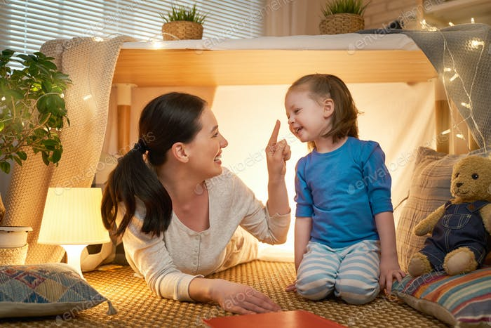 mother and daughter playing in tent