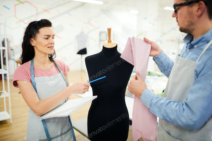 Young female student asking professional tailor about fabric