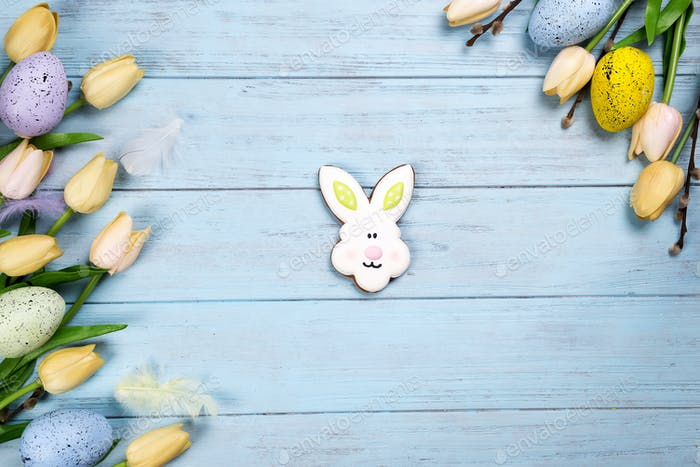 Happy Easter colorful cookies bunny on wooden blue background.