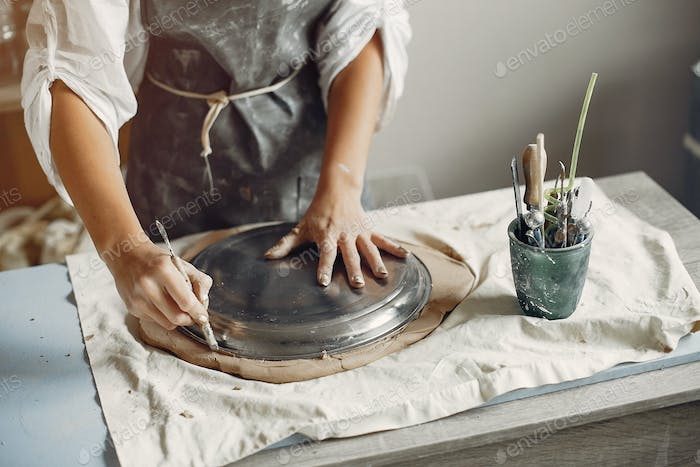 A young woman makes dishes in a pottery