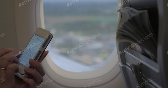Woman typing sms in flying plane