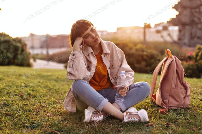 Sad young woman sits on grass in city during sunset. Short-haired girl in jeans and pink denim jack