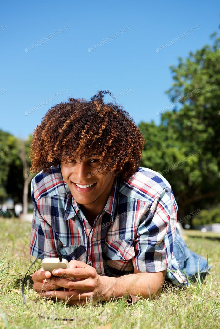 smiling young afro man lying down on grass in park holding phone