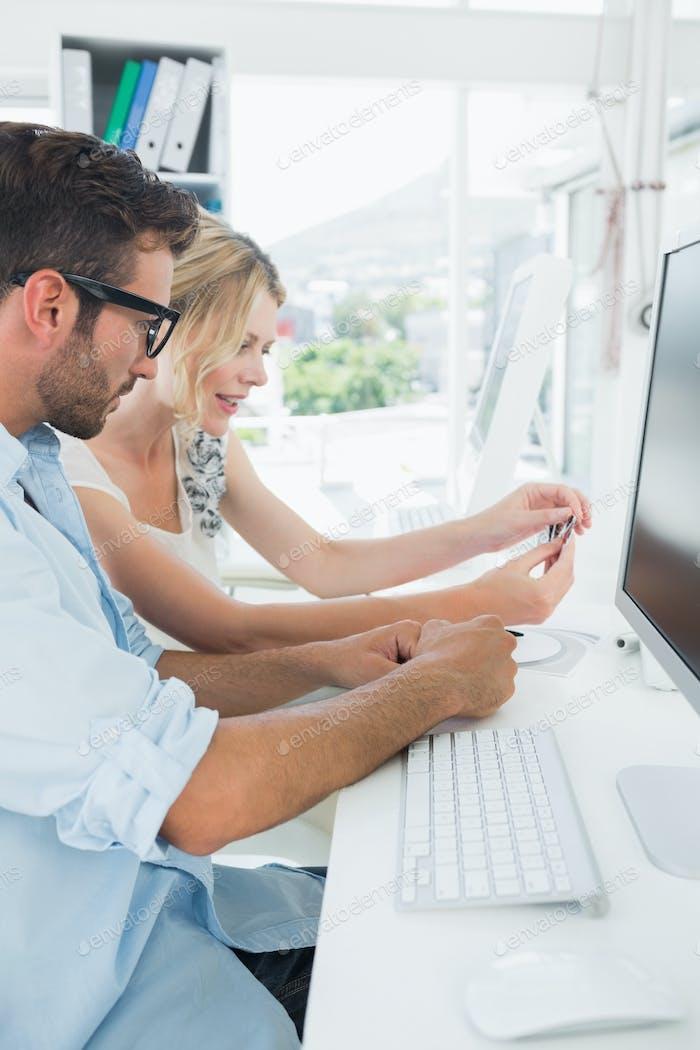 Seitenansicht der lächelnden lässig jungen Paar arbeiten am Computer in einem hellen Büro