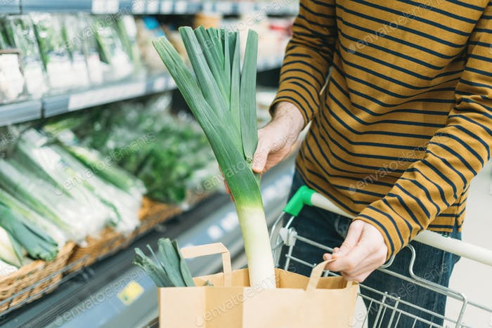 Man in vegetable department at supermarket puts leeks in paper bag