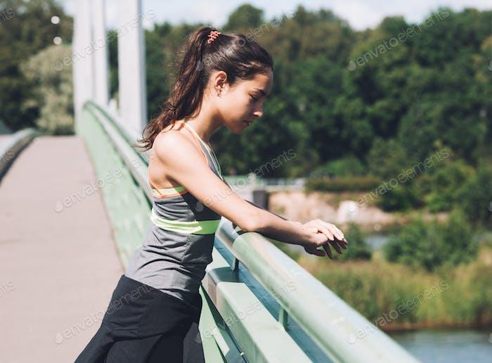 Sport. Frau zurück in Sportkleidung auf Brücke Sommer Blick auf Wasser