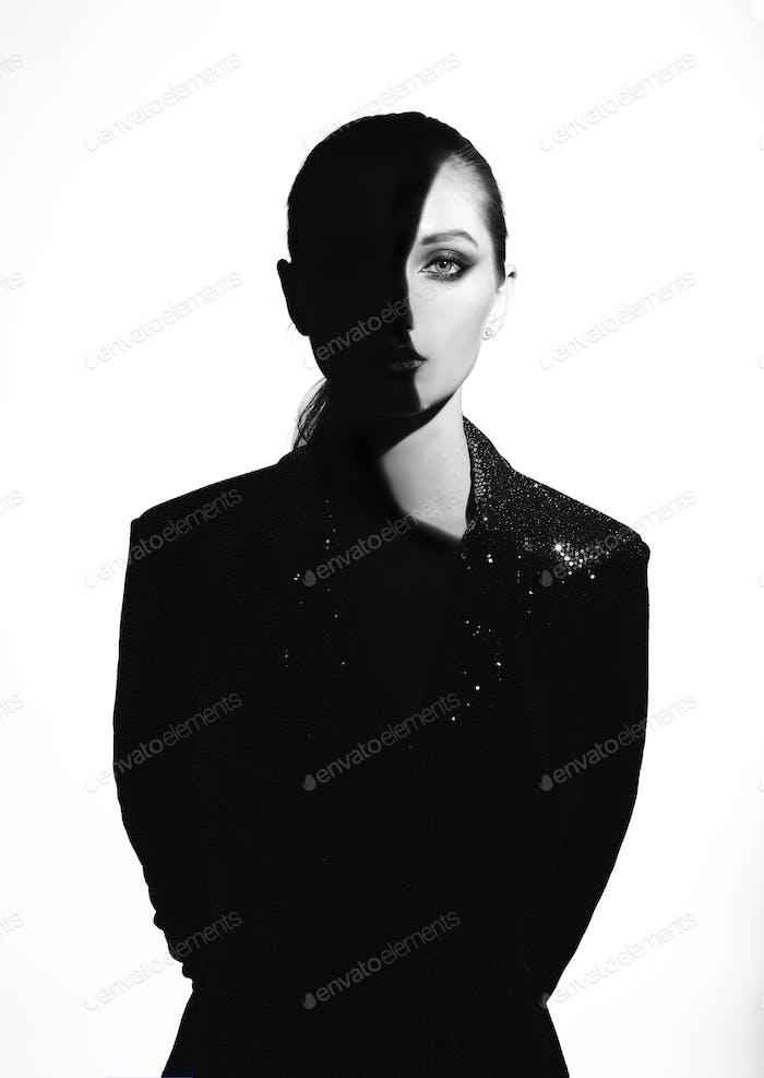 Black and white portrait of trendy girl with hair pulled back and stylish makeup in a shining dress