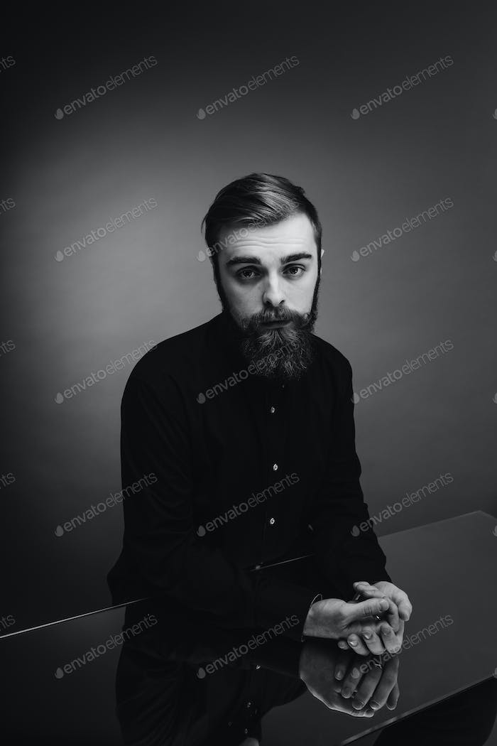 Black and white photo of a man with a beard and stylish hairdo dressed in the black shirt standing
