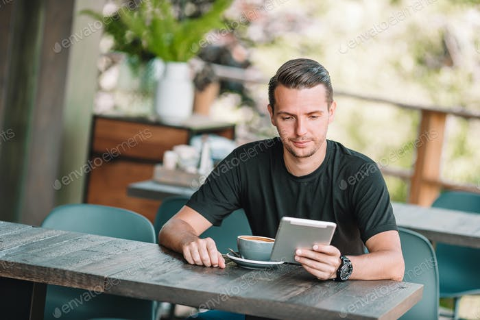 Young man with laptop in outdoor cafe drinking coffee