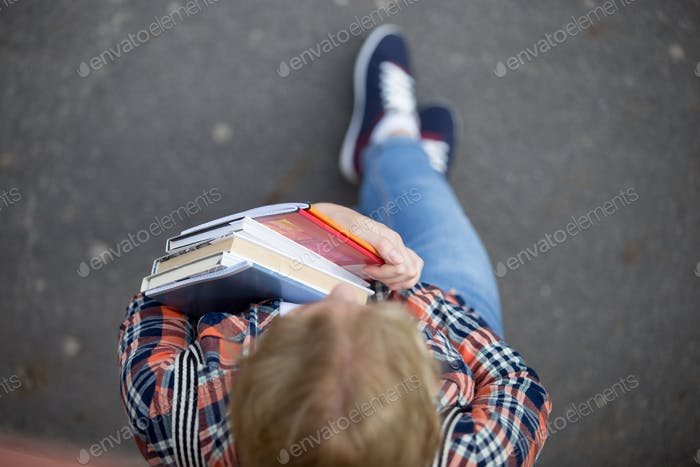 Student lady with a heap of textbooks and notebooks