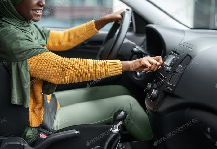 Unrecognizable black muslim woman turning on volume in car audio system