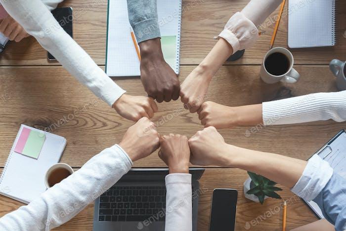 Internationale Gruppe von Geschäftsleuten, die Fäuste in den Kreis