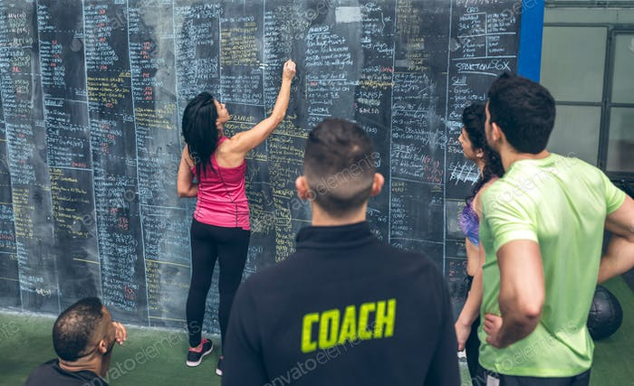 Athlete woman writing down results on the gym blackboard