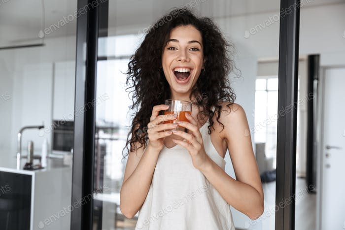Photo of excited curly woman with long dark hair smiling at you,
