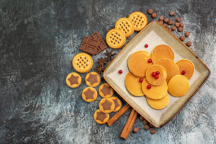 top shot of yummy round pancakes with delicious sweets on grey background