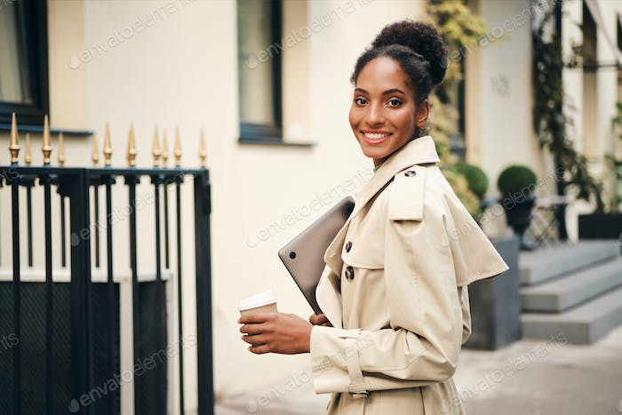 Smiling African American business woman in trench coat joyfully looking in camera outdoor