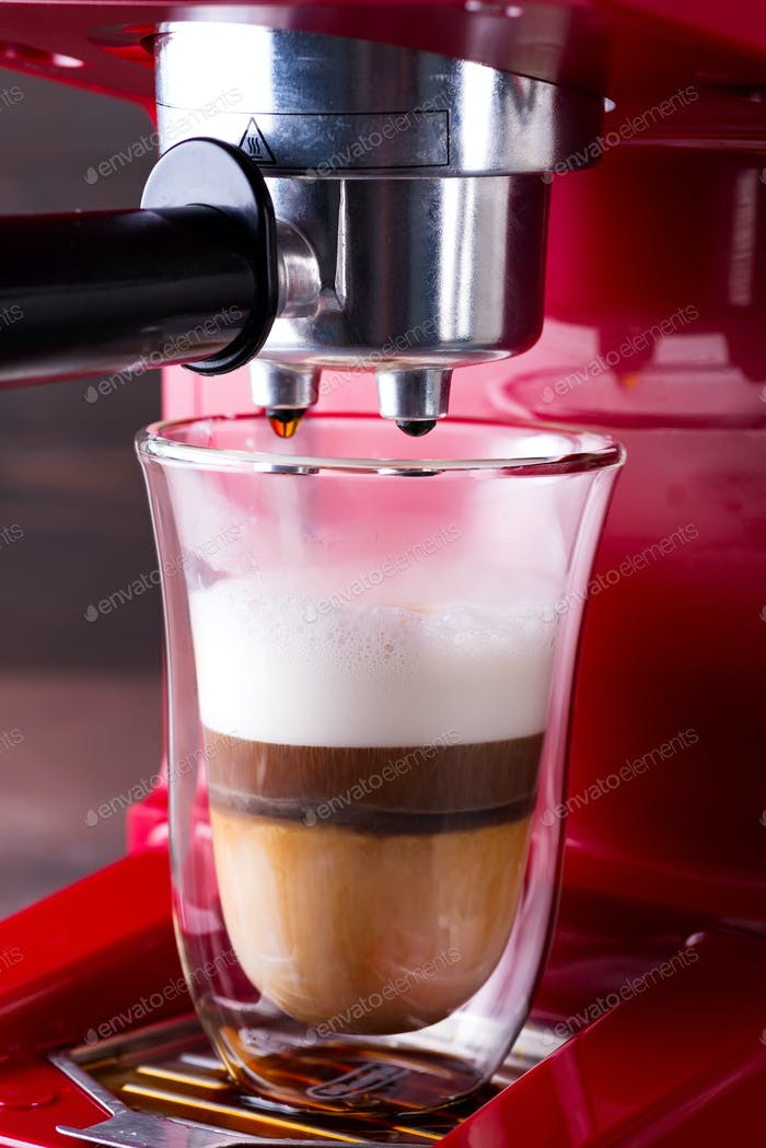 Coffee machine preparing cappuccino in double glass, close up