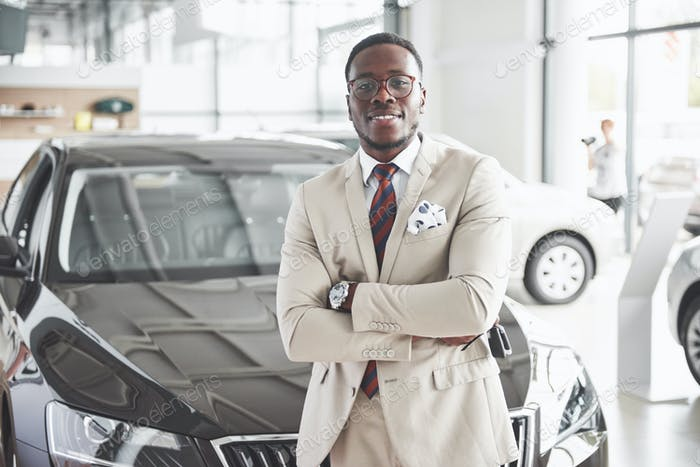 The young attractive black businessman buys a new car, dreams come true