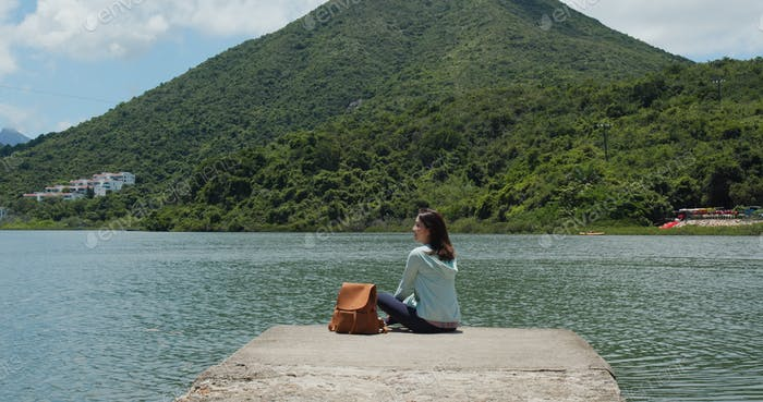 Mujer con mochila mira alrededor de la montaña y vista al mar