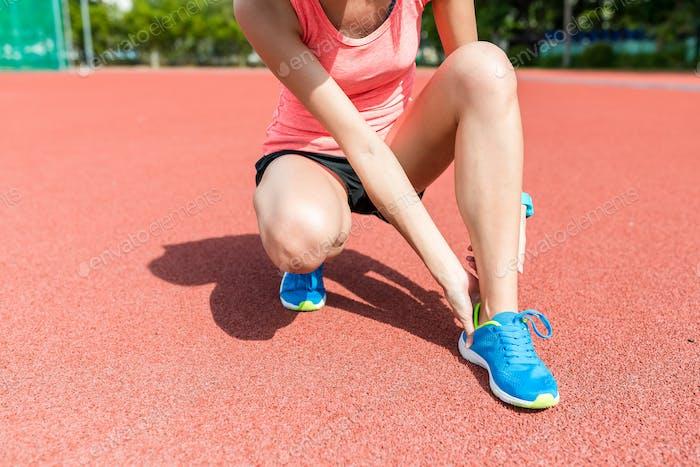 Sport woman getting hurt on legs in sport stadium