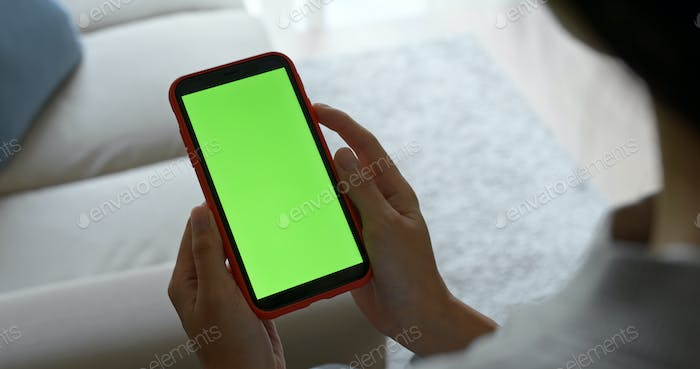 Woman hold cellphone with green screen