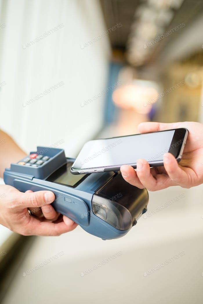Mujer paga por tecnología NFC