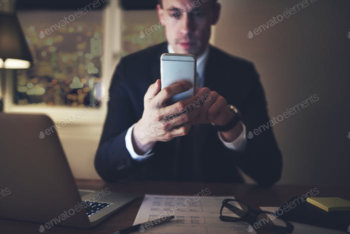 businessman browsing phone in evening office