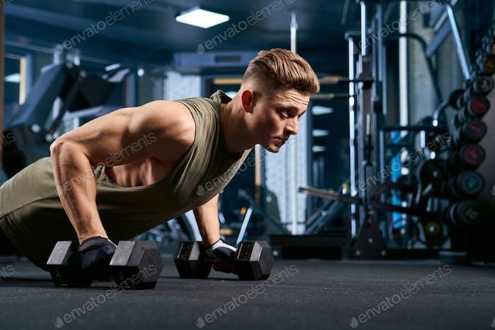 Muscular man doing push ups using dumbbells
