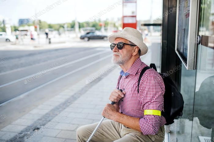 Senior blind man with white cane waiting for public transport in city.