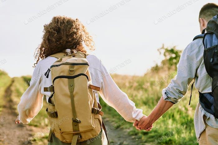 Rückansicht der jungen weiblichen Tragerucksack, während sie ihren Mann von Hand hält