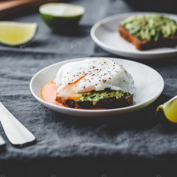 Avocado sandwich with rye bread and a poached egg on a plate