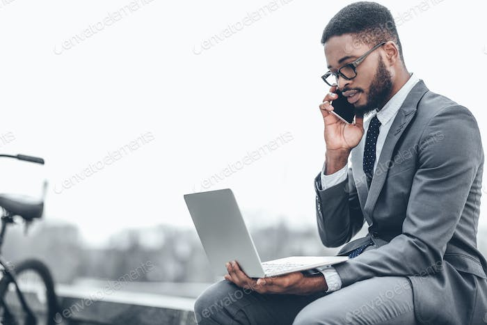 Confident businessman talking on phone and using laptop